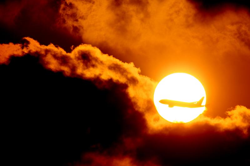 夕暮れの太陽に飛行機の機影が飛び込んできた瞬間